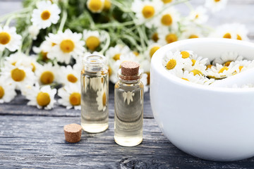 Bottle of chamomile oil with mortar and flowers on wooden table