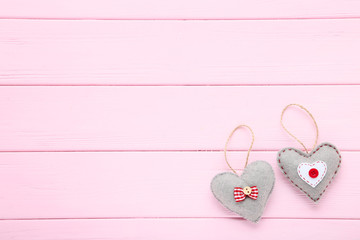 Grey fabric hearts on pink wooden table