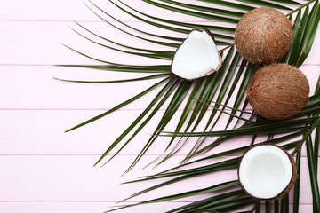 Ripe coconuts with palm leafs on pink wooden table