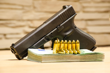 The pistol with bullets stays behind money with bllured wall backspace