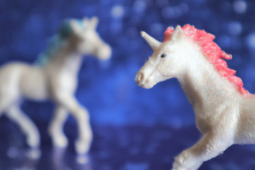 Two magical unicorn on a blue backgroun