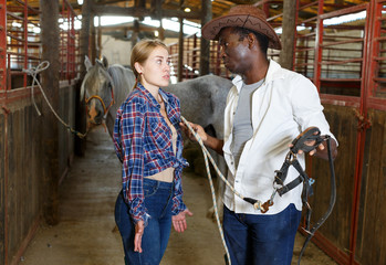 Girl and man having emotional discussion at stable