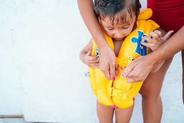 A mother helping daughter with her life jacket