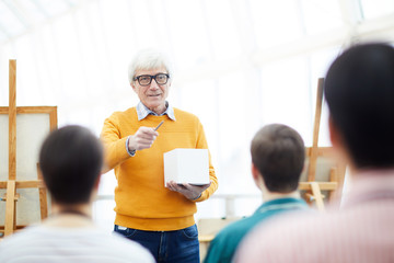 Portrait of senior art teacher talking to group of students during lecture in college, copy space