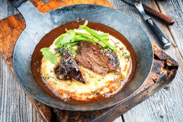 Traditional German braised veal cheeks in brown sauce with mashed potatoes and beans as closeup in a wrought-iron pan