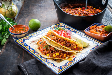 Traditional slow cooked Mexican chili con cane with tortillas as closeup on a colored plate