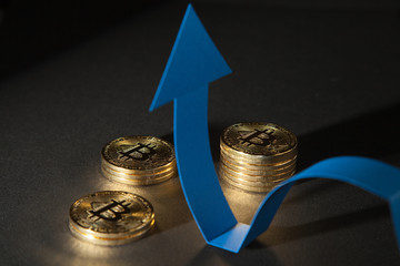 Shiny bitcoins and blue arrow showing up