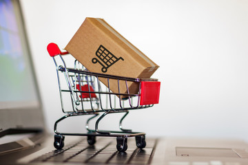 Shopping cart with Carton on computer keyboard. Online shopping, e-commerce and worldwide shipping concept