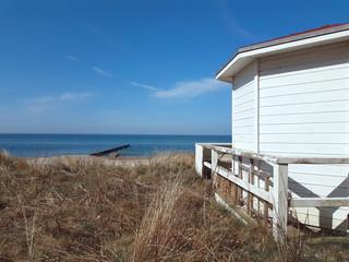 white beach hut at dune landscape