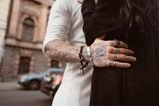 The man's hand in tattoos and jewelry embraces a girl's waist.