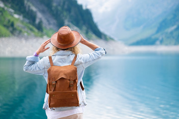 Traveler-Image. Traveler look at the mountain lake. Travel and active life concept. Adventure and travel in the mountains region in the Austria.