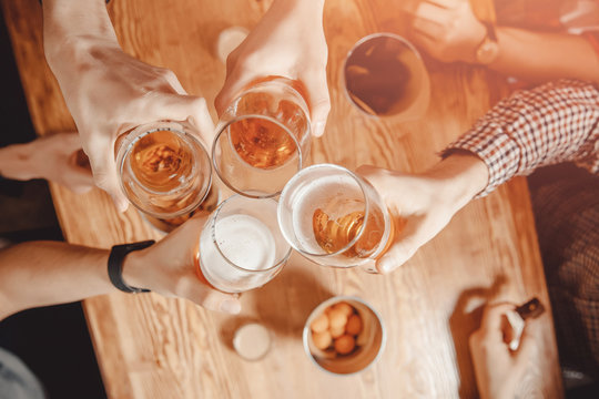 Cheerful and happy old friends are drinking draft beer at pub bar clink glasses. Top view. Friendship concept