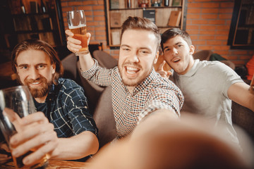 Cheerful friends make selfie photos and drink draft beer at pub bar. Friendship concept