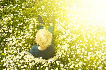 Blonde Child Sitting In A Daisy Flower Meadow