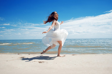 Young beautiful jumping brunette woman in white dress