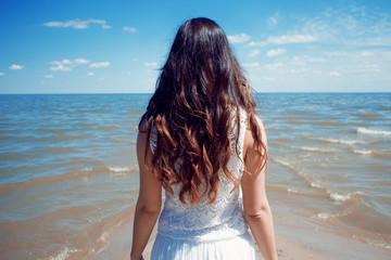 Fotobehang Bleke violet Young beautiful brunette woman in white dress on the seashore.