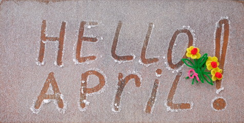 "The inscription ""Hello April!"" on wooden background. Letters in the snow."
