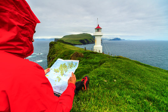 Hiker on cliffs looks at the map next to lighthouse, Mykines island, Faroe Islands, Denmark