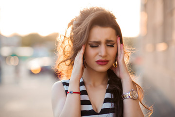 Emotional girl with face expression holding hands with headache posing with closed eyes. Beautiful brunette woman have stress and pain, walking posing at street. Fashionable girl in striped dress.