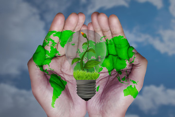 save energy, with bulb on hand, blue sky background