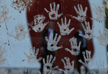 Security guards of Brazilian mining company Vale SA are seen through hand prints made from mud during a protest in front of Vale SA headquarters in Rio de Janeiro