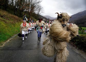A man dressed as a bear accompanies bell-wearing dancers known as Joaldunak during carnival celebrations in Ituren