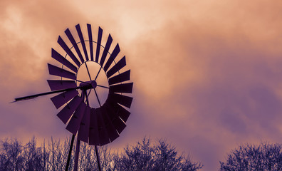 vintage decoration, a classic old rusty windmill at sunset, colorful sky and clouds, agricultural or western background