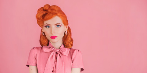 Advertise cosmetics. Woman smile with pink lipstick in retro dress. Minimal color trend in design. Redhead model with red lips advertise cosmetics on pink background. Bright lipstick. Minimal style