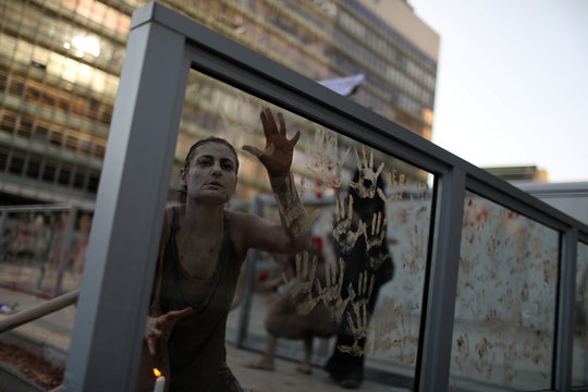An activist covered in mud puts her hand prints at the front of the Brazilian mining company Vale SA headquarters, during a protest in Rio de Janeiro