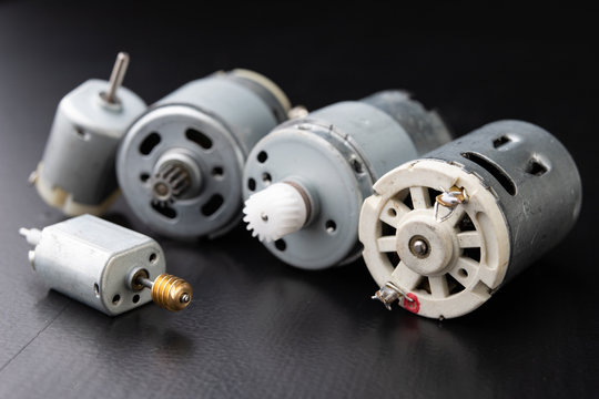 Small electric engine on a wooden dark table. Electric drive for small home appliances.