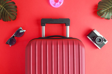Luggage with summer vacation accessories on red.
