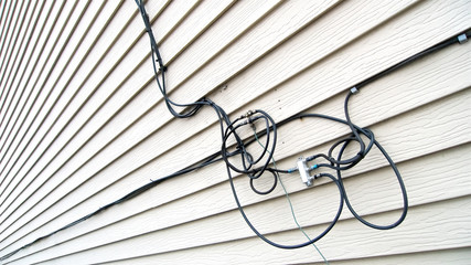 A tangle of telecommunications wires and cables attached on the siding of a residentail property for service installation and access.