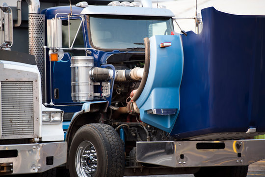Blue big rig semi truck with open hood standing on the parking lot for repair engine and service work