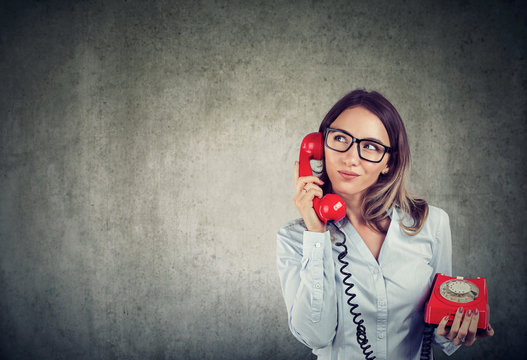 Business woman with an old fashioned tellephone carefully listening to a customer