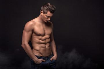 Handsome shirtless man in studio.