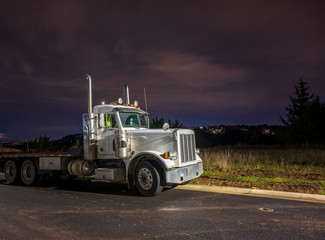 Old big rig day cab semi truck with flat bed semi trailer stand on parking at night time with dark Northwest sky