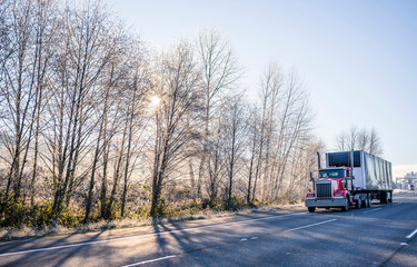 Red big rig day cab American semi truck transporting cargo in covered semi trailer driving on winter frosty road with sunshine