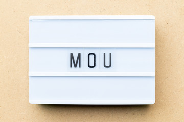 White lightbox with word MOU (Abbreviation of memorandum of understanding) on wood background