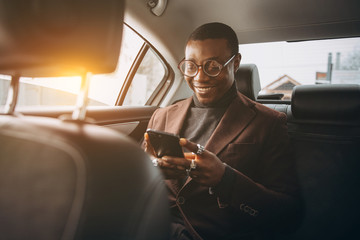 Young smiling african man using smartphone while sitting on backseat in car. Concept of happy business people traveling. Wall mural