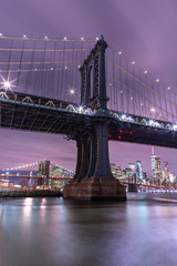Person at the east river pier with view on Manhattan Bridge and Financial district at night