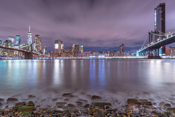 Night view from East river beach on Financial district and Manhattan, Brooklyn Bridges with long exposure