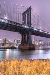 View on Manhattan Bridge and Financial District at night from East River with long exposure