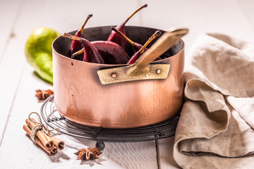 Mulled wine with pears and cinnamon on white table