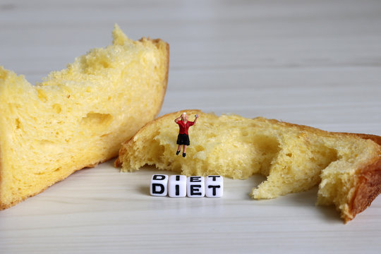 Weight control and diet concept. A miniature woman sitting on the bread doing makeup.
