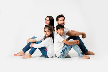Young Indian/asian family sitting isolated over white background. selective focus