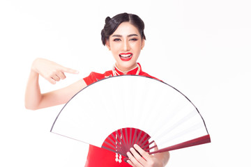 Charming beautiful Chinese woman pointing finger to copy space of Chinese fan. Attractive beautiful girl showing something that makes her happy and enjoy it with smile face. She wear Chinese dress