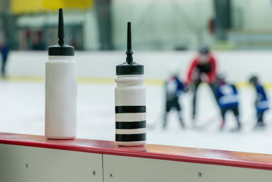 Two white water bottles on the boarder of hockey arena. Blurred Silhouette of the Kids hockey team on the background