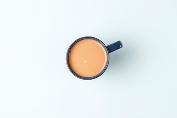 Cup of coffee on a blue background, top view, copy space