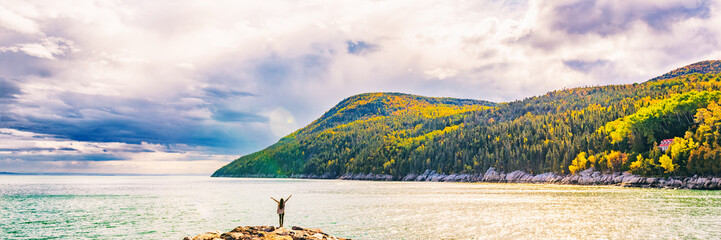 Autumn Fall nature landscape mountains banner background in Quebec, Canada. St Lawrence river in Charlevoix region, North America. Tourist person with arms up open in freedom happy of travel holidays.