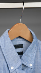 Mens blue button up shirt hanging in closet, denim